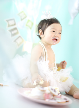 女の子の赤ちゃんがケーキを触っている写真