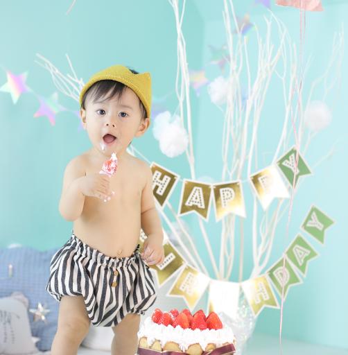 男の赤ちゃんがケーキを食べている写真