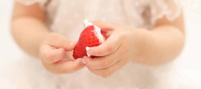 赤ちゃんがイチゴを持っている手元の写真